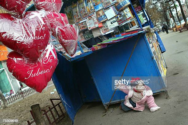 A child plays on the ground next to a newspapers stand and hearts reading in Romanian 'I Love You' one day ahead of the celebration of Valentine's...
