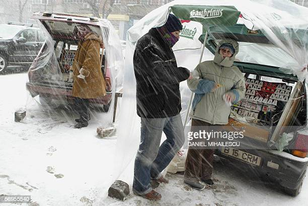 A Romanian couple stands under a plastic sheet to protect them from the blizzard as they try to sell from the trunk of their car handmade Martisor...