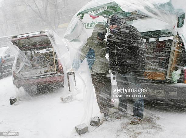 A Romanian couple stands under a plastic sheet to protect them from the blizzard as they try to sell from the boot of their car handmade Martisor...