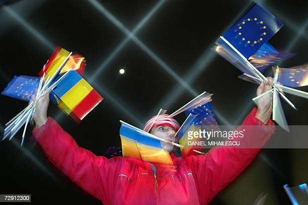 A Romanian youth holds EU and Romanian flags at a New Year celebration party in Piata Universitatii Square in Bucharest 01 January 2007 Former...