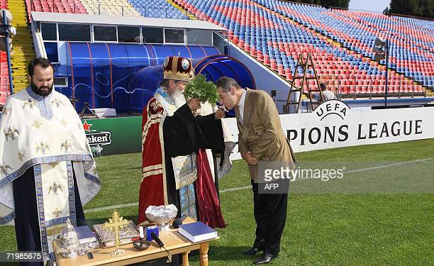 Steaua's Bucharest club owner Gigi Becali kisses a cross while a Romanian orthodox priests bless the Steaua's stadium, one day ahead of the Champion...