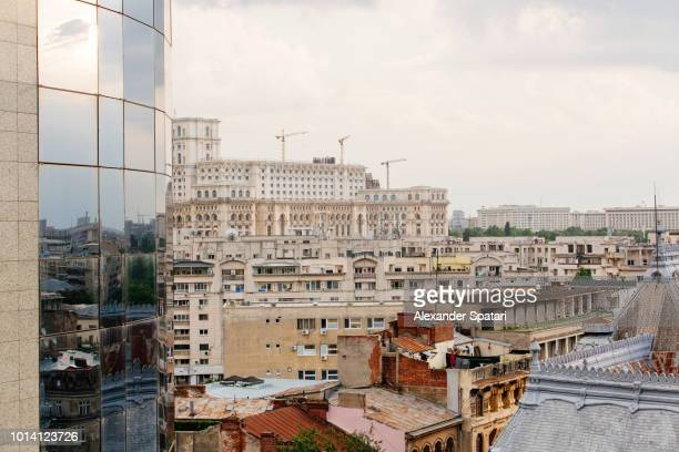 Bucharest skyline with new office building, Palace of Parliament and old communist block houses