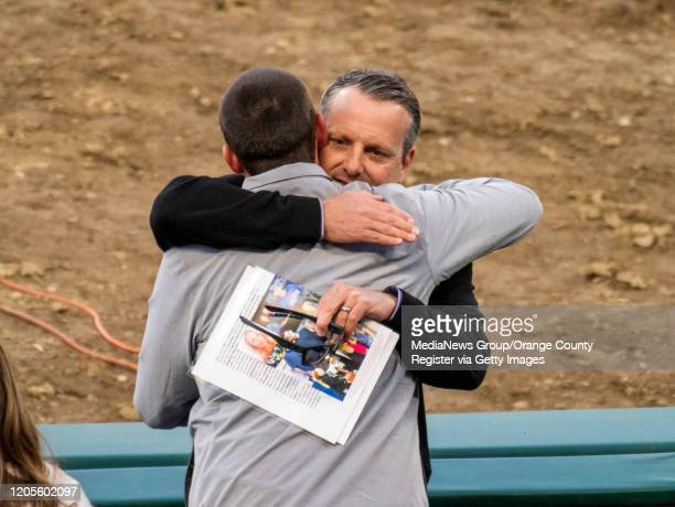Buck Taylor right who coached against John Altobelli and a friend of the family embraces JJ Altobelli after he gave a speech the memorial service for...