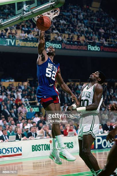 Buck Williams of the New Jersey Nets dunks against Robert Parish of the Boston Celtics during a game played in 1989 at the Boston Garden in Boston...