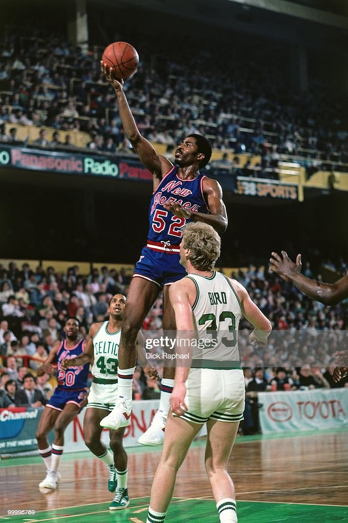 Buck Williams #52 of the New Jersey Nets shoots a layup against Larry Bird #33 of the Boston Celtics during a game played in 1983 at the Boston Garden in Boston, Massachusetts.