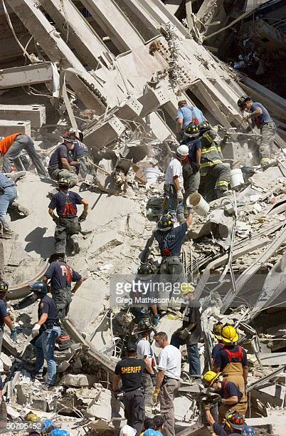 Bucket brigade working to clear rubble and debris, hoping to find survivors after World Trade Center was destroyed during a terrorist attack.
