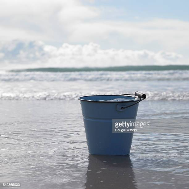 bucket full of water at beach.. - dougal waters stock pictures, royalty-free photos & images