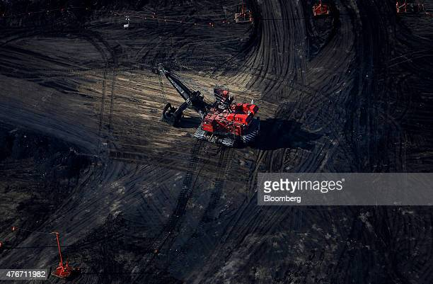 A bucket loader digs for oil sands at the Suncor Energy Inc mine in this aerial photograph taken near Fort McMurray Alberta Canada on Thursday June 4...
