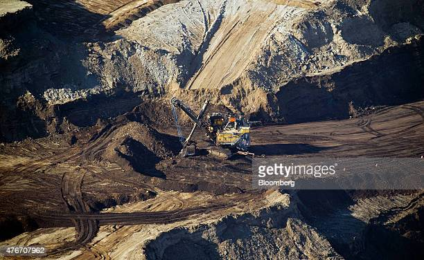 A bucket loader digs for oil sands at the Syncrude Canada Ltd mine in this aerial photograph taken near Fort McMurray Alberta Canada on Thursday June...