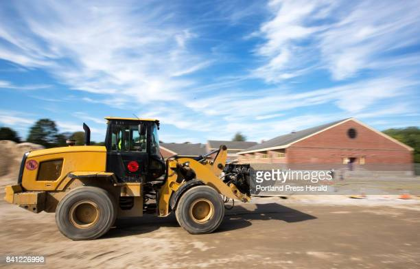 A bucket loader drives a load of sand across the sprawling construction site at Saccarappa Elementary School Students will have to contend with...