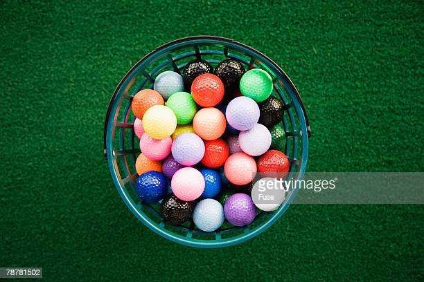 bucket of colorful golf balls - golf humour photos et images de collection