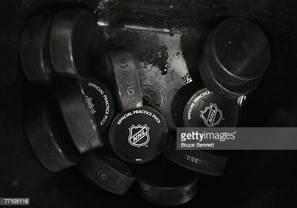 A bucket of NHL official practice ice hockey pucks in a bucket at a practice session for the Los Angeles Kings and the Anaheim Ducks ice hockey teams...