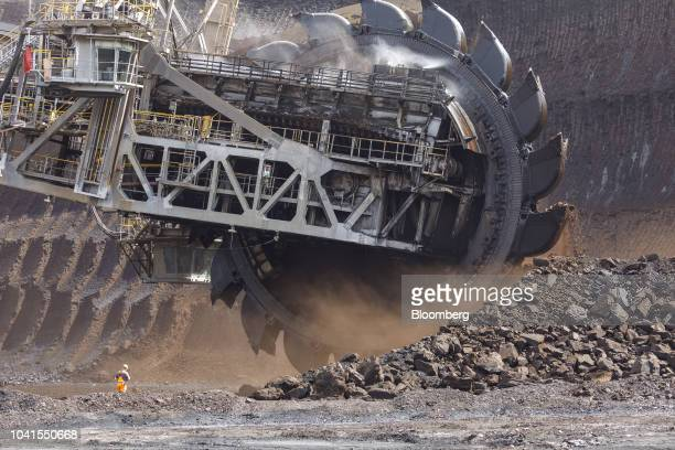 A bucket wheel excavates soil and rocks as a giant excavator operates at the open pit lignite mine operated by RWE AG in Hambach Germany on Monday...