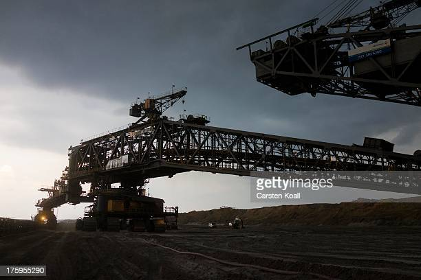 A bucket wheel excavator mines lignite coal at dusk in the Welzow openpit lignite coal mine on August 10 2013 near Welzow Germany The mine operated...
