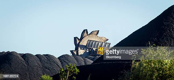A bucket wheel reclaimer operates behind stockpiles of coal at the Newcastle Coal Terminal in Newcastle north of Sydney Australia on Friday May 3...