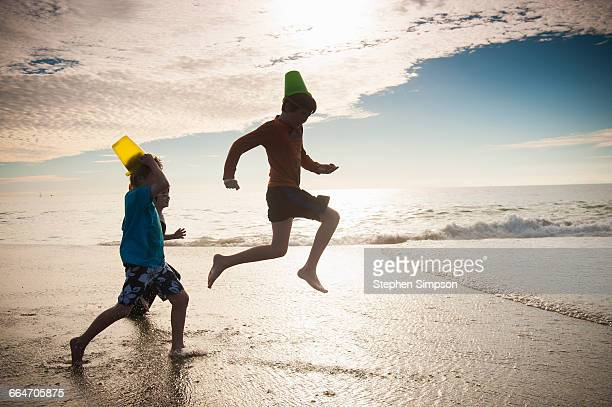 """""""buckethead"""" boys running and leaping at the beach - la jolla stock pictures, royalty-free photos & images"""