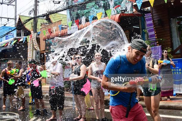 Buckets of water are thrown on a parade participant during the Songkran festival on April 13 2015 in Chiang Mai Thailand The Songkran festival...
