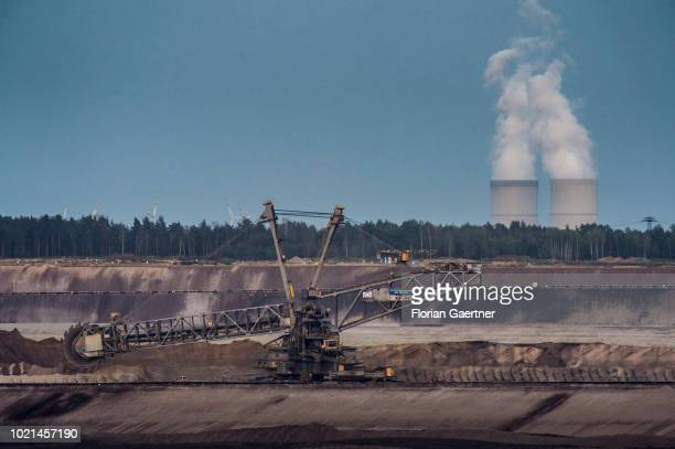 A bucketwheel excavator of the opencast mining 'WelzowSued' is pictured in front of the lignitefired power station 'Schwarze Pumpe' on August 22 2018...