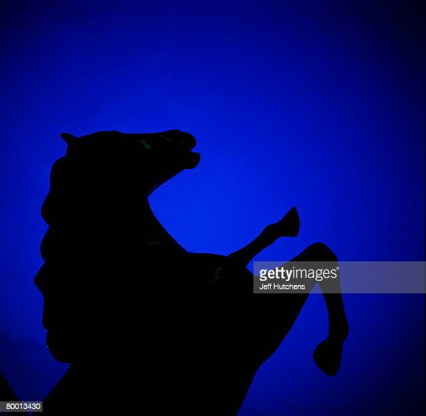 A bucking fiberglass horse statue is silhouetted against the night sky at South of the Border on July 21 2006 in Dillon South Carolina Nearly...