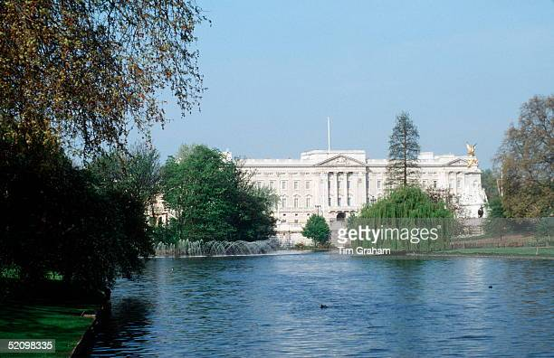 Buckingham Palace From St James Park Opposite Showing The Lake Trees And A Fountain