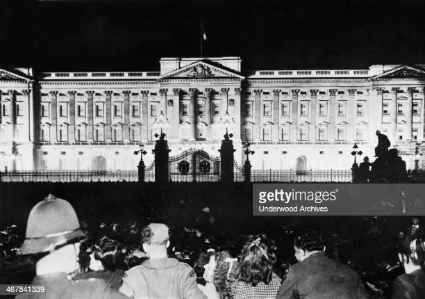 Buckingham Palace is illuminated with floodlights as London celebrates VE Night at the close of the war London England May 1945 The crowd is...