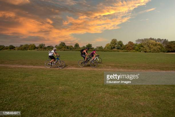Buckinghamshire, England, UK, Cyclists riding across an area known as the Brocas in Eton, with a glowing colored sky as sunset approaches.
