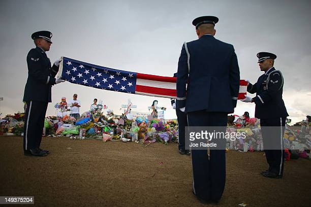Buckley Air Force base Mile High Honor Guard folds an American flag at a memorial setup across the street from the Century 16 movie theatre on July...