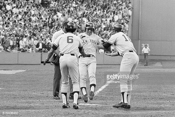 Bucky Dent is a happy fellow as he jumps on home plate and is greeted by Roy White and Chris Chambliss after he hit a three-run home run in the 7th...