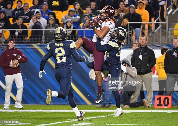 Bucky Hodges of the Virginia Tech Hokies makes a catch in front of Ryan Lewis and Terrish Webb of the Pittsburgh Panthers in the second half during...