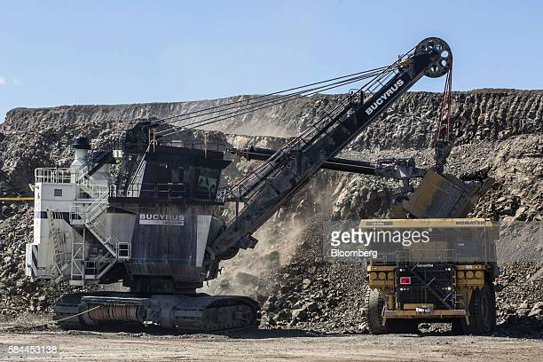 A Bucyrus Inc excavator loads a Komatsu Ltd dump truck in an open pit at the Oyu Tolgoi coppergold mine jointly owned by Rio Tinto Group's Turquoise...