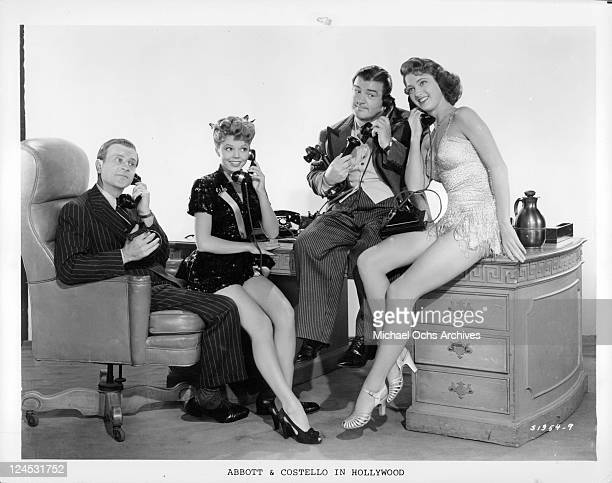 Bud Abbott and Lou Costello sit on phone next to ladies in a scene from the film 'Bud Abbott And Lou Costello In Hollywood' 1945
