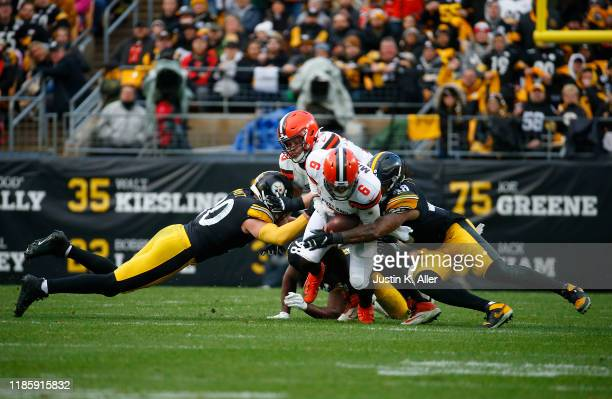Bud Dupree and T.J. Watt of the Pittsburgh Steelers strip sacks Baker Mayfield of the Cleveland Browns in the second half on December 1, 2019 at...
