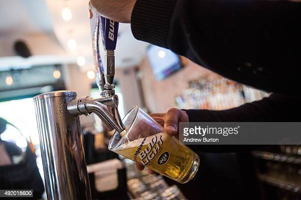 A bud light beer is poured from the tap at a bar on October 9 2015 in New York City Budweiser's parent company AB InBev is attempting to buy SABMiller