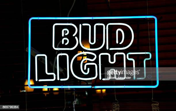 Bud Light neon sign hangs in the window of a store in New York, New York.