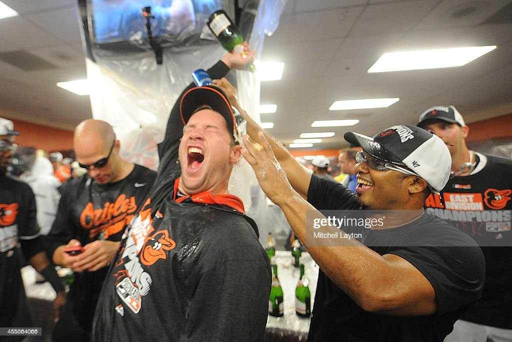 Bud Norris #25 (L) and Alejandro De Aza #12 (R) of the Baltimore Orioles celebrate in locker room after the Orioles clinch the American League East Division after a baseball game against the Toronto Blue Jays on September 16, 2014 at Oriole Park at Camden Yards in Baltimore, Maryland.