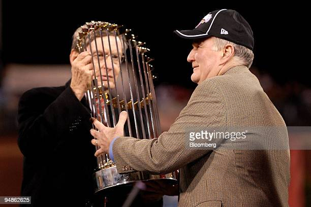 Bud Selig commissioner of Major League Baseball left hands the championship trophy to David Montgomery owner of the Philadelphia Phillies after the...