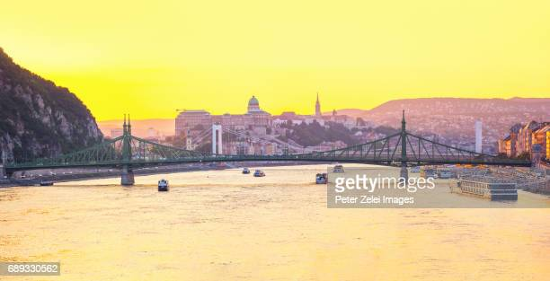 Budapest cityscape at sunset with the Liberty and Elizabeth bridges, and the Buda Castle in the background