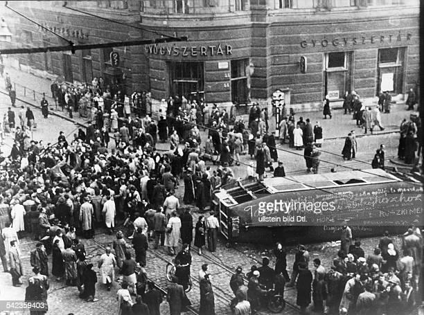 Budapest: Ein umgestürzter Strassenbahnwagenist mit antikommunistischen Parolenbeschrieben worden. Links im Bild eineMenschengruppe um die Überreste...