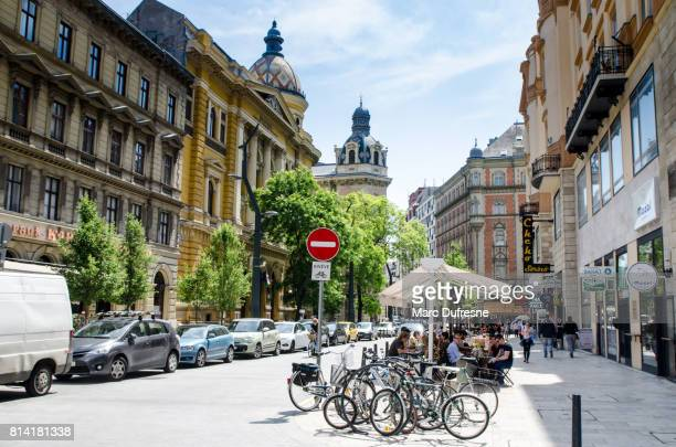 Budapest Ferenciek street with people eating on a restaurant patio with bikes standing in front of them