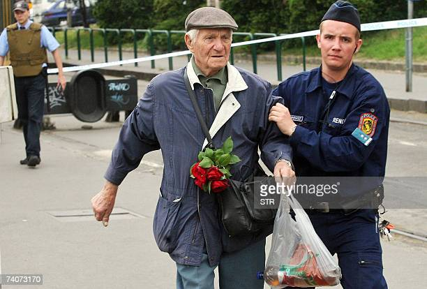 A policeman helps an elderly man 04 May 2007 in front of an office of the largest Hungarian bankchain the 'OTP Bank' at the Szena square of Budapest...