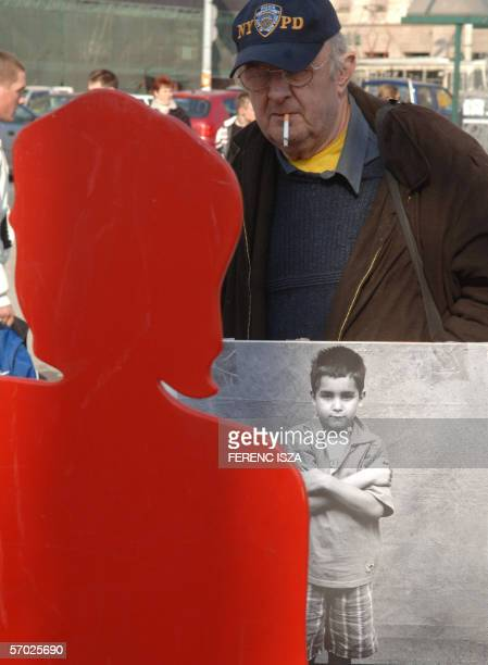 """An man looks sporting a sandwich board, looks at a red cut-out of a woman 08 March 2006 as associations,Amnesty International, """"NANE"""", women's rights..."""
