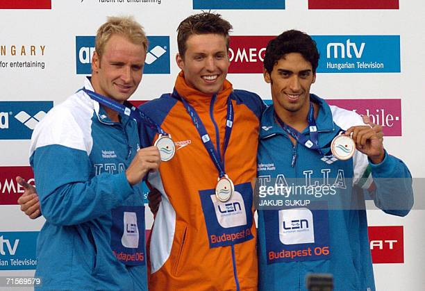 Dutch Pieter Van den Hoogenband celebrates on the podium with Italy's Massimiliano Rosolino and Filippo Magnini after winning the men's 200m...
