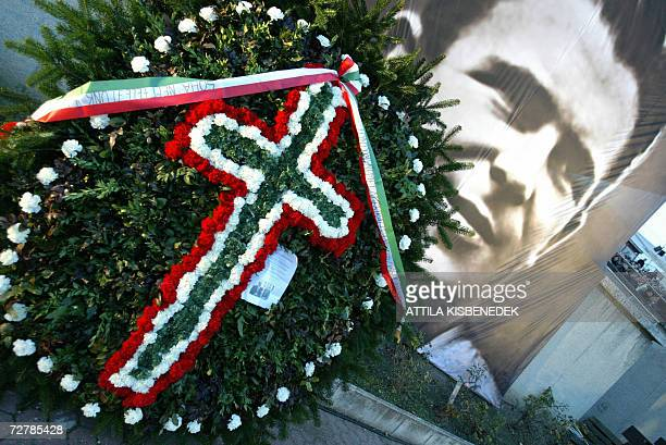 Flowers lay in front of a giant portrait of football legend Ferenc Puskas prior to a ceremony at the stadium bearing his name in Budapest 09 December...