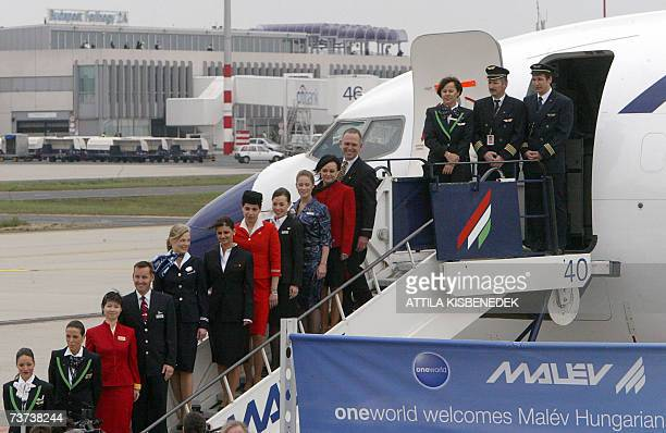 Pilots, stewards and stewardesses of the member airlines of the Oneworld alliance pose on stairs 29 March 2007 at the Ferehegy airport of Budapest...