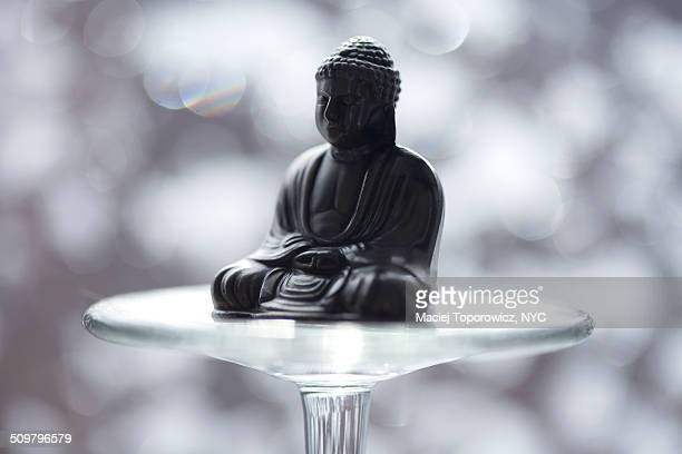 Budda figurine sitting on a glass stem