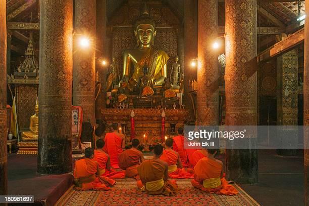 Buddha and monks inside Wat Xieng Thong