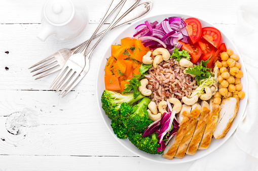 Buddha bowl dish with chicken fillet, brown rice, pepper, tomato, broccoli, onion, chickpea, fresh lettuce salad, cashew and walnuts. Healthy balanced eating. Top view. White background 924491746