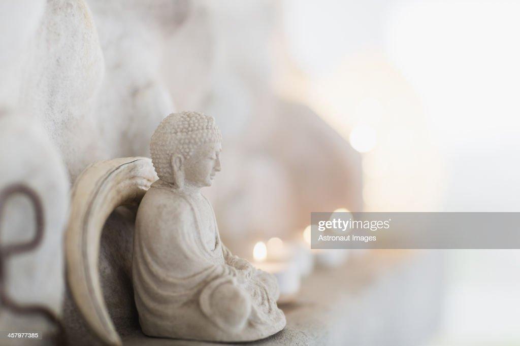 Buddha figurine and candles on ledge : Stock Photo