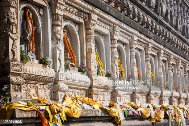 buddha sculpture with french marigolds offered by pilgrims on the mahabodhi temple, bodhgaya, gaya, bihar state, india - buddha state stock pictures, royalty-free photos & images