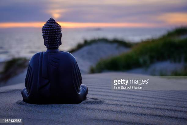 buddha sitting i the sand. dunes and ocean in the background. sunset with beautiful colors over the ocean - philosophy stock pictures, royalty-free photos & images